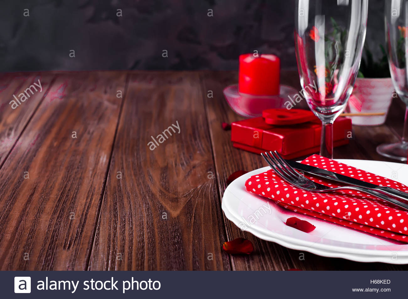 Romantic Valentine Candle Light Dinner Table Setting with red roses gift and burning candles against a brown background. & Romantic Valentine Candle Light Dinner Table Setting with red roses ...