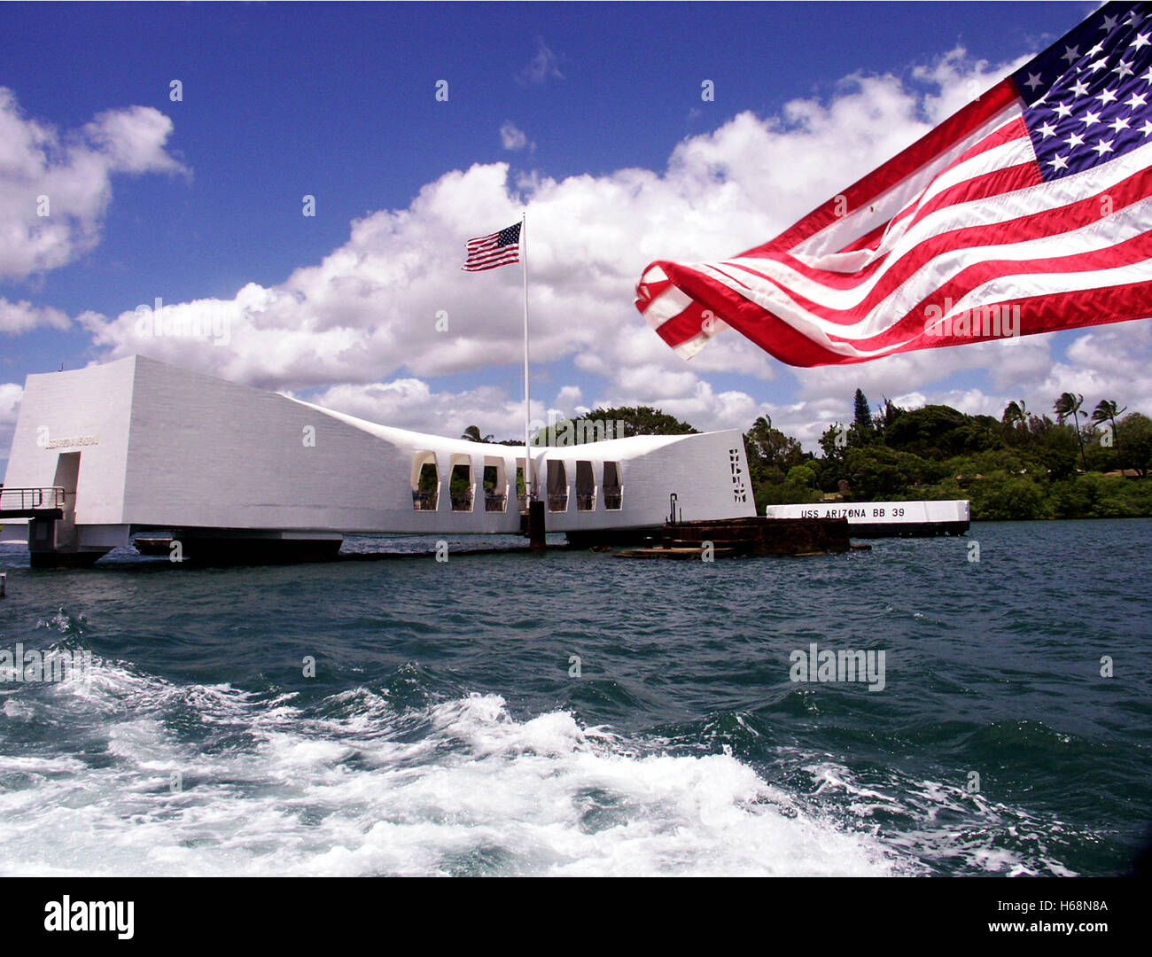 View of the USS Arizona Memorial in Pearl harbor with an American Flag waving in the foreground complementing the Stock Photo