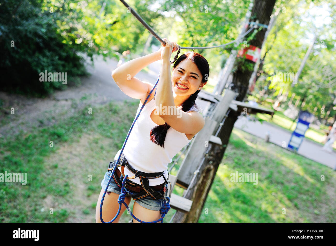 Asian girl passes obstacles ropes course - Stock Image