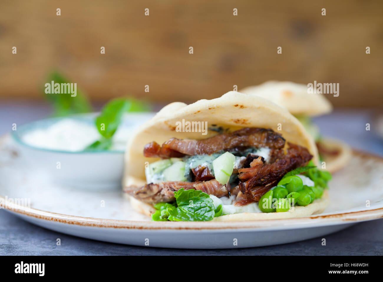 Mini flat breads with crispy lamb, mashed peas, cucumber, mint and yogurt sauce - Stock Image