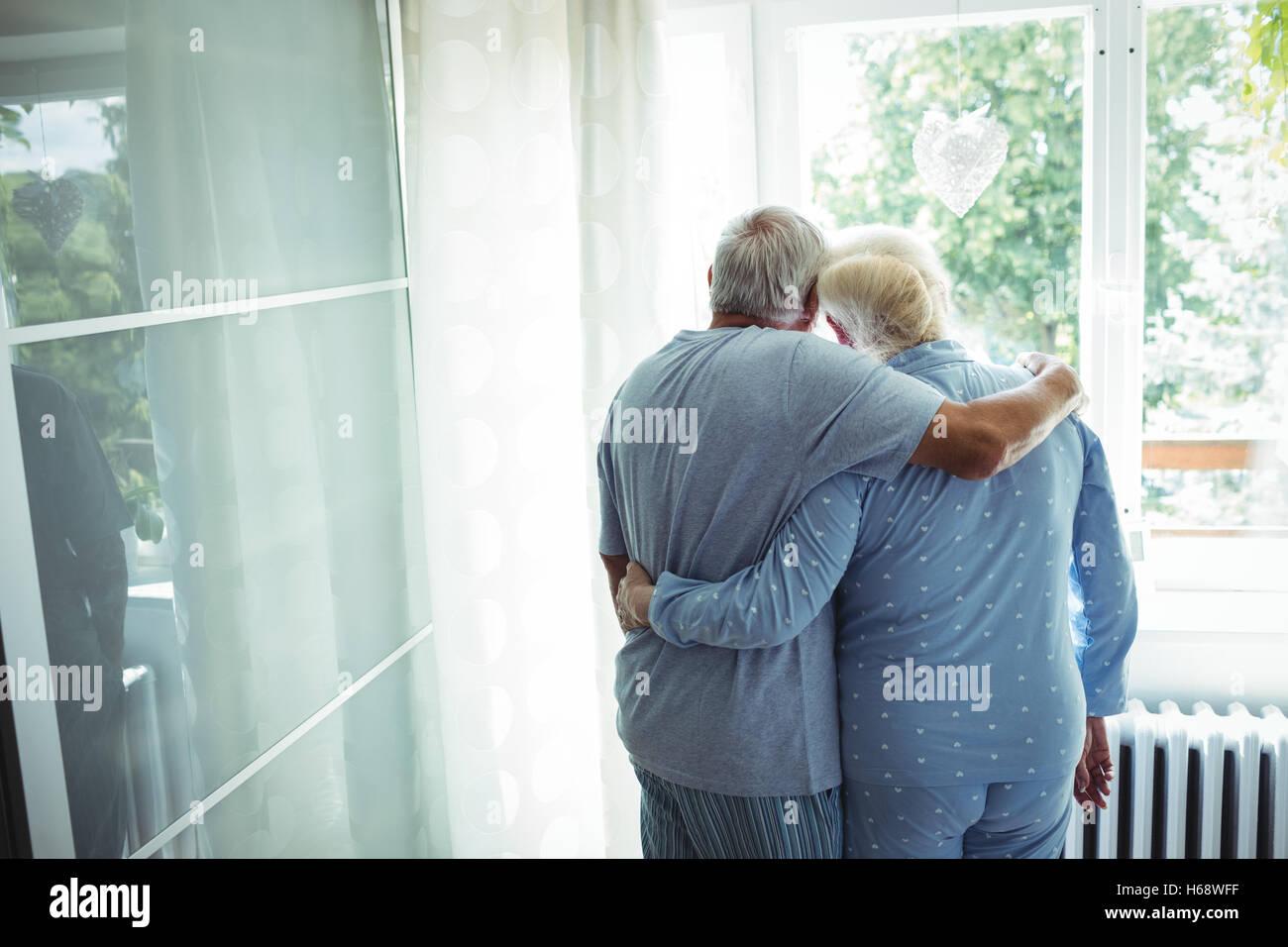 Senior couple standing with arms around - Stock Image