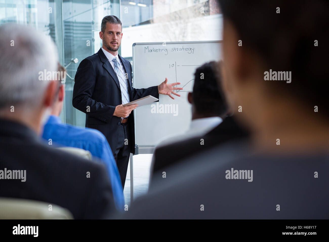 Businessman discussing on white board with co-workers - Stock Image