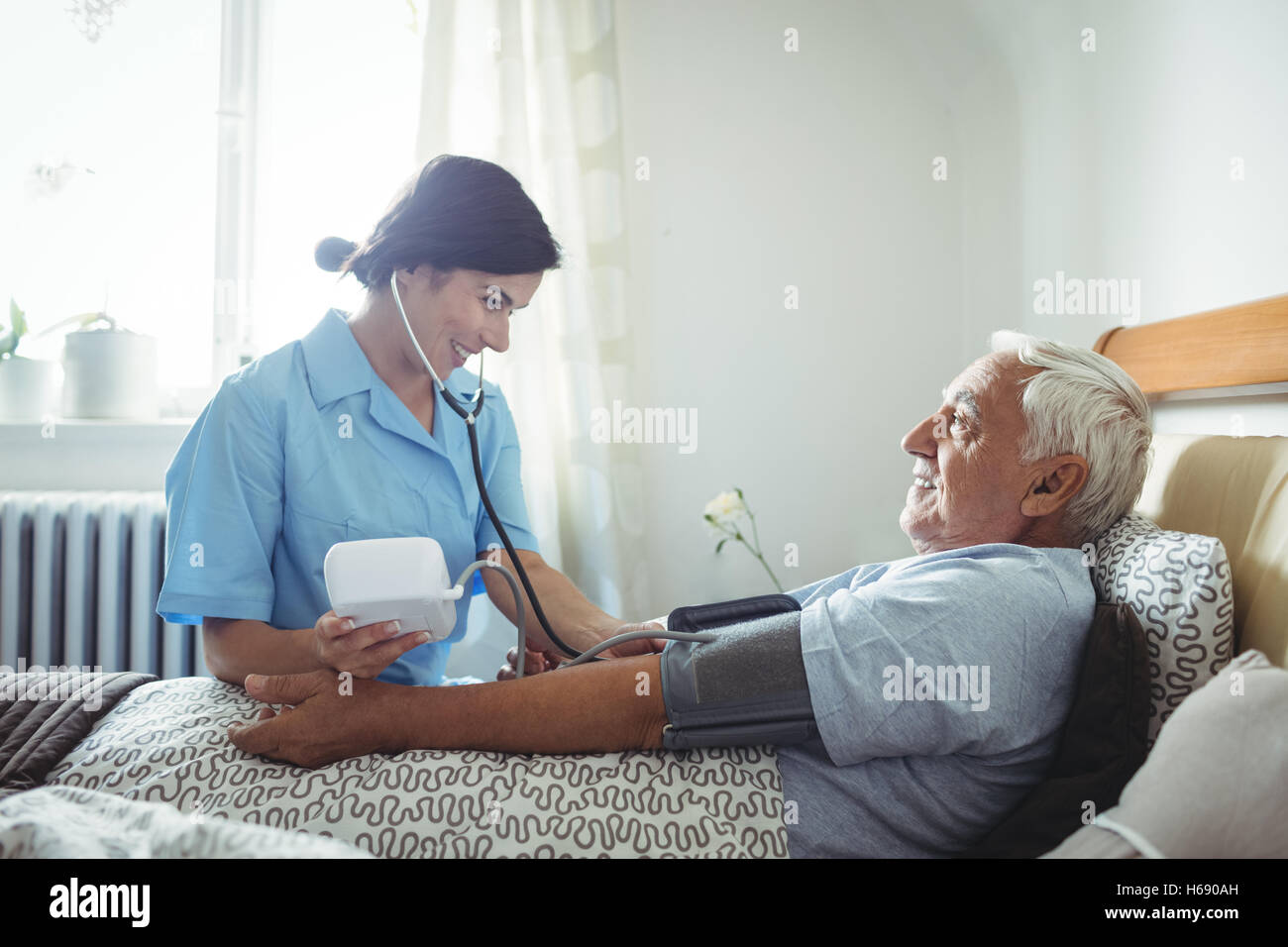 Nurse checking blood pressure of senior man - Stock Image