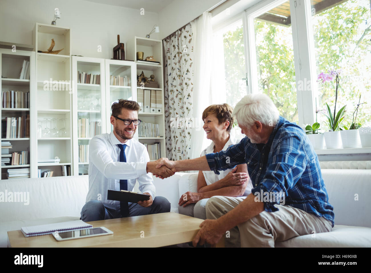 Financial advisor shaking hands with senior man - Stock Image