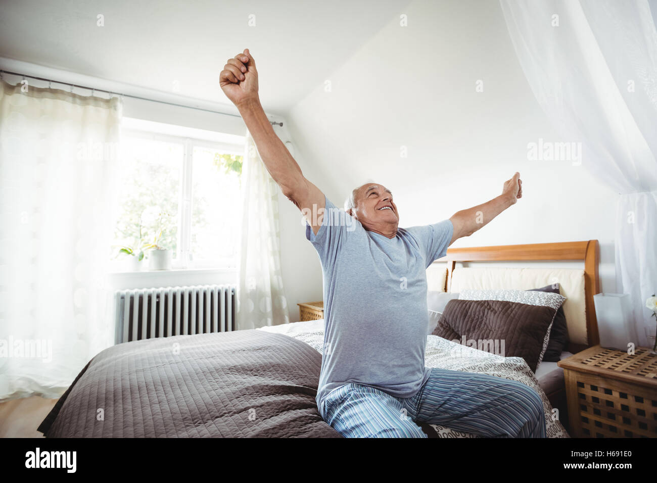 Senior man yawning on bed - Stock Image