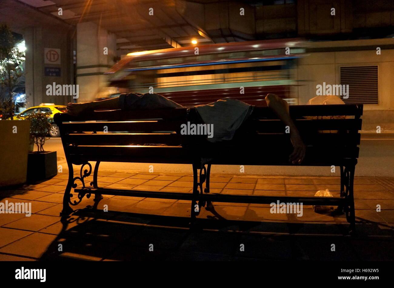 A homeless man sleeps on a bench under the BTS railtracks in Bangkok, Thailand. - Stock Image