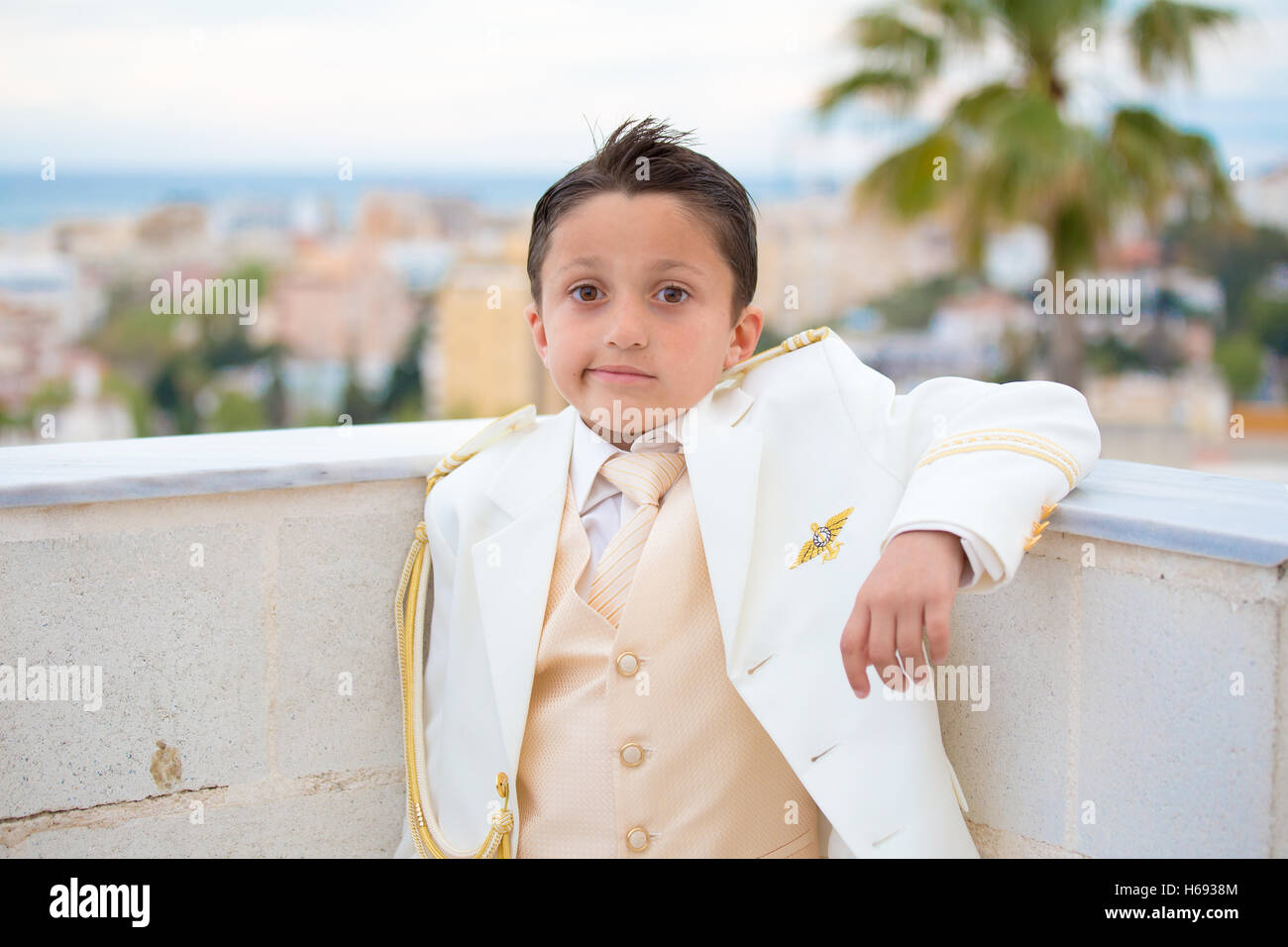 Young boy with white suit leaning on a wall with his elbow in his First Communion. - Stock Image