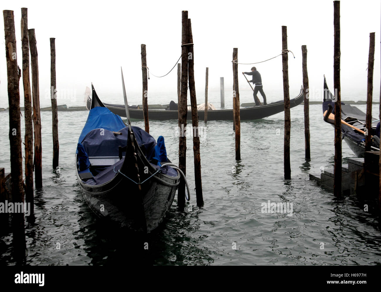 `A misty morning in Venice provides the classic view of gondolas and gondolier - Stock Image