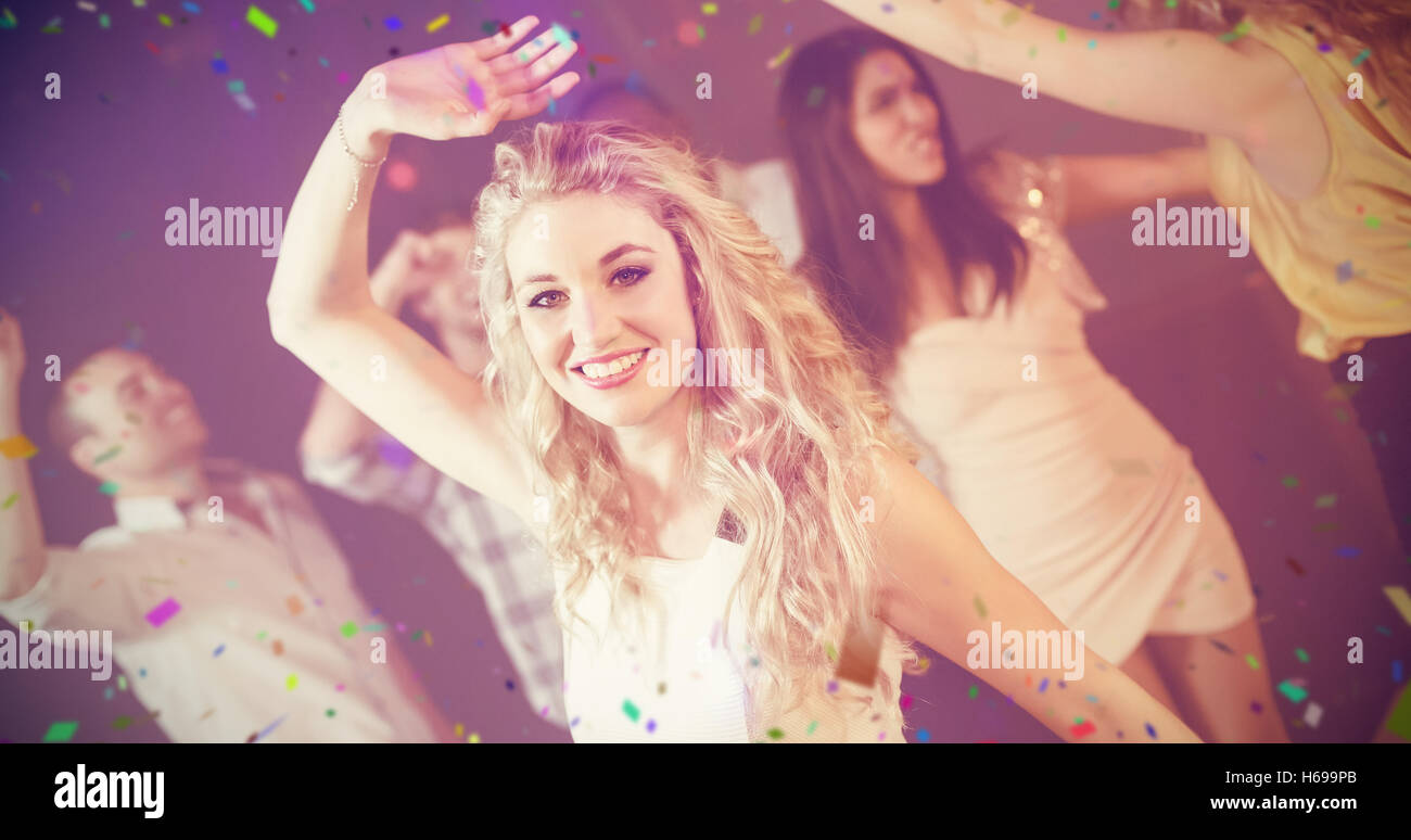 Composite image of happy friends dancing cheerfully - Stock Image