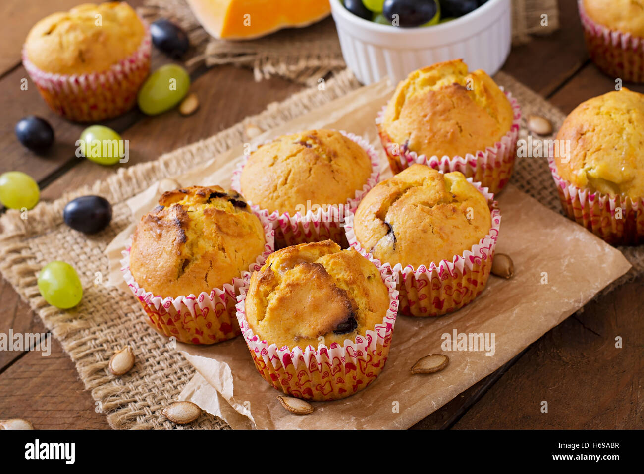 Appetizing and ruddy muffins with pumpkin and grapes - Stock Image