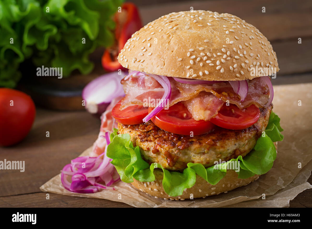Big sandwich - hamburger burger with beef, red onion, tomato and fried bacon. - Stock Image