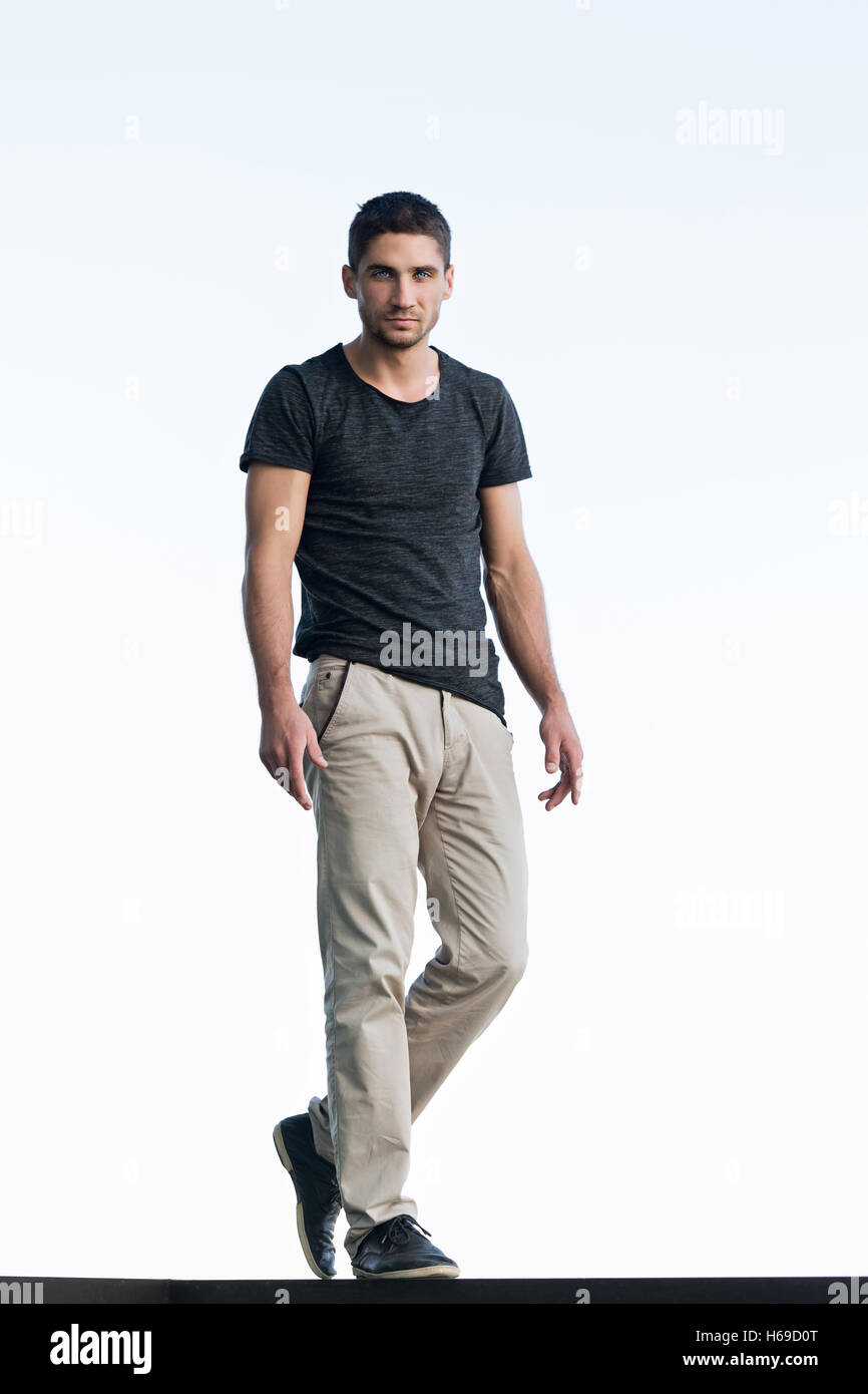 Athletic man in a dark T-shirt against the sky. Men's beauty. Street fashion. - Stock Image