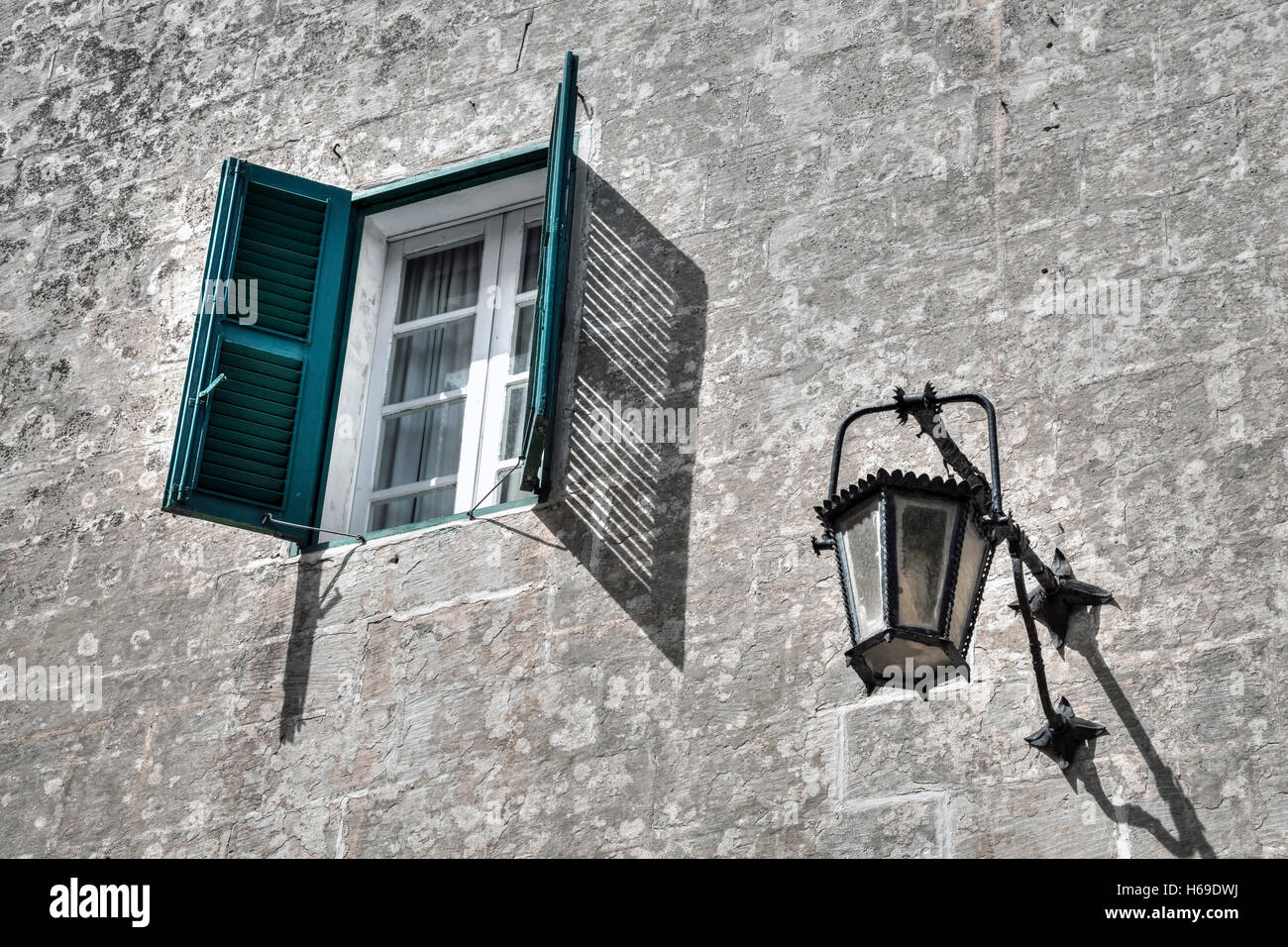 a window with green shutters and a lantern on an old house - Stock Image