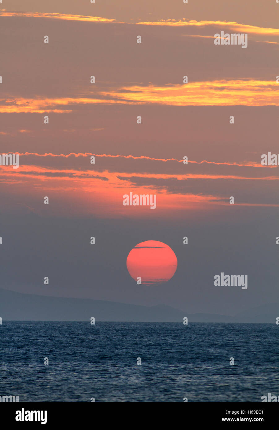 Sunset over the ocean with clouds and water with copy space - Stock Image