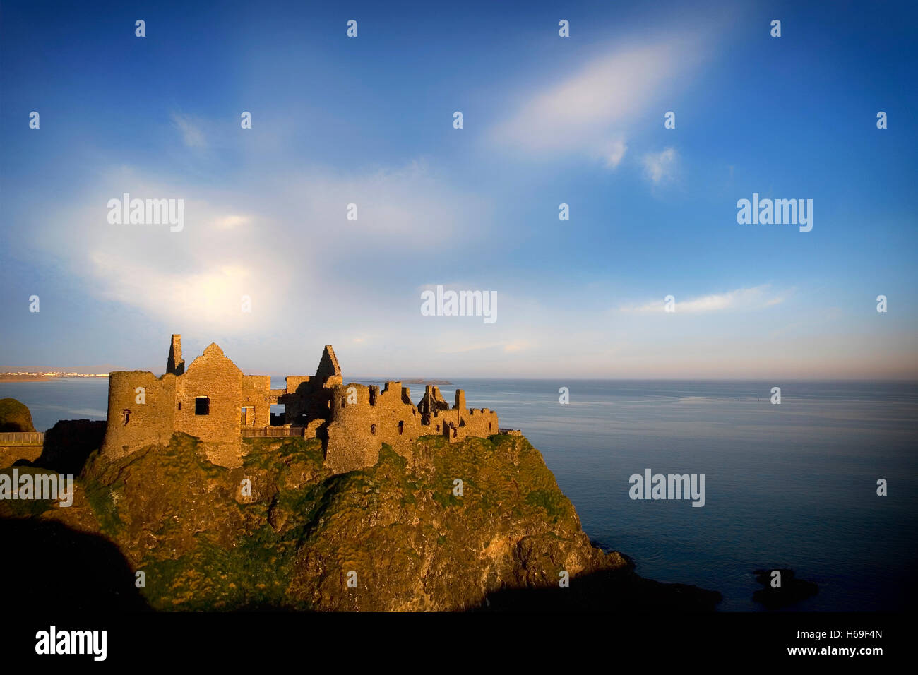 Ruined medieval Dunluce Castle, located on the edge of a basalt outcrop between Portballintrae and Portrush, County - Stock Image