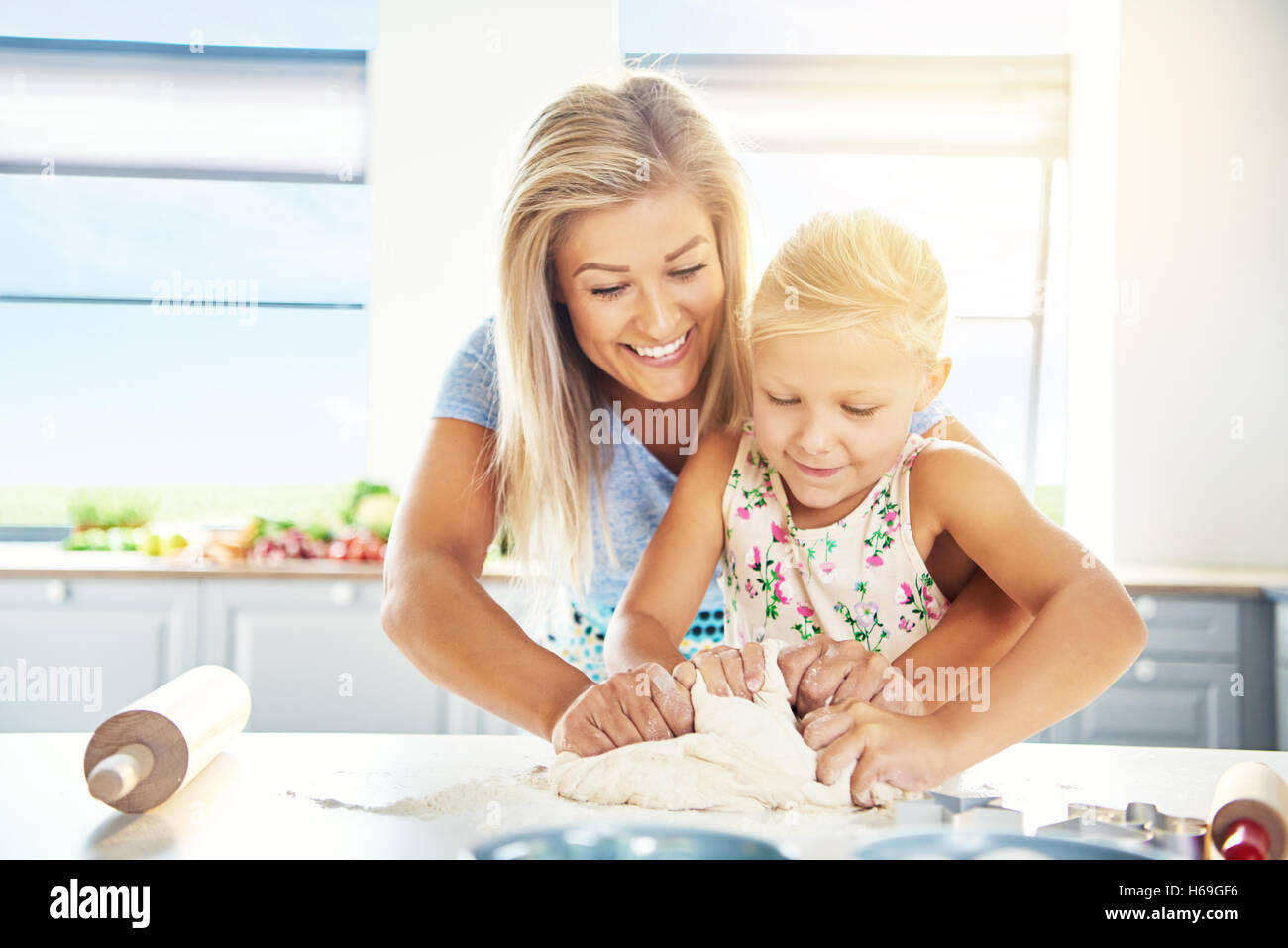 Adoring young mother teaching her daughter to bake as they stand together at the kitchen table kneading the dough - Stock Image