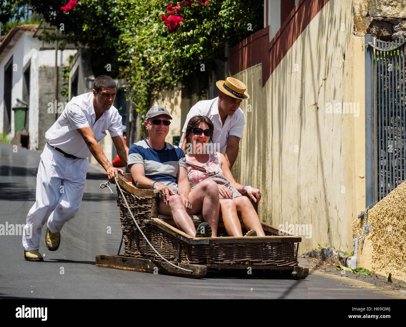 Toboggan drivers dressed in traditional white clothing carry tourists in a wooden toboggan from Monte down the hill - Stock Image