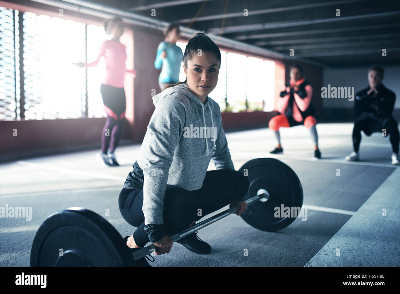 Fit healthy woman exercising, sitting at floor looking at camera, getting ready to lift weight - Stock Image