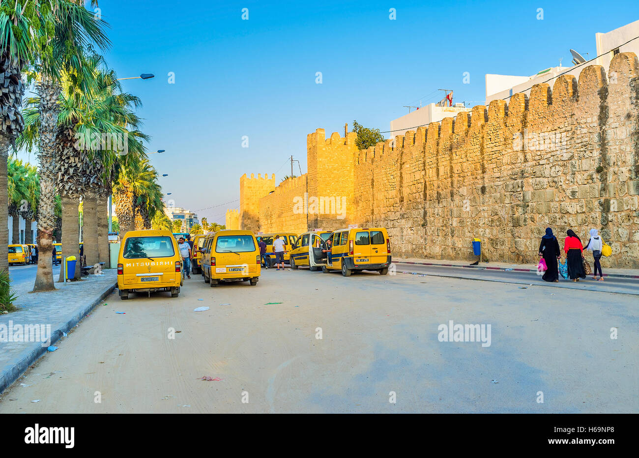 The noisy and crowded minibuses stop next to Medina walls Stock Photo