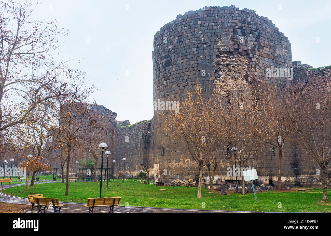 The city garden stretches along the old town wall with its numerous black basalt towers, Diyarbakir, Turkey. - Stock Image