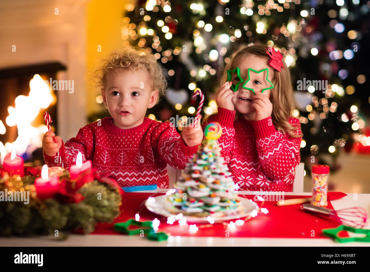 Little Boy And Girl Making Christmas Gingerbread House At