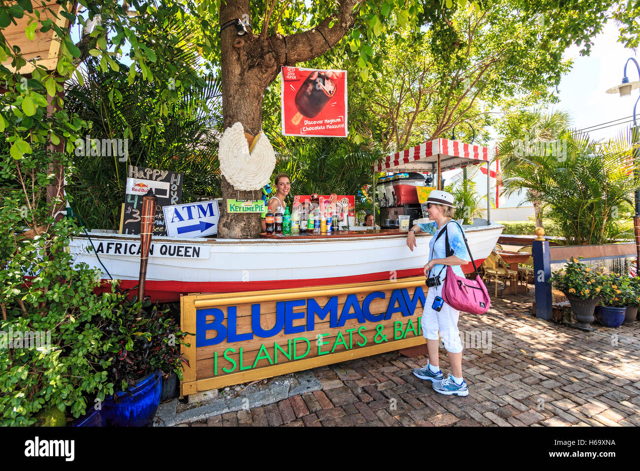 Woman stops to buy drink at outdoor, roadside bar in Key West, Florida. - Stock Image