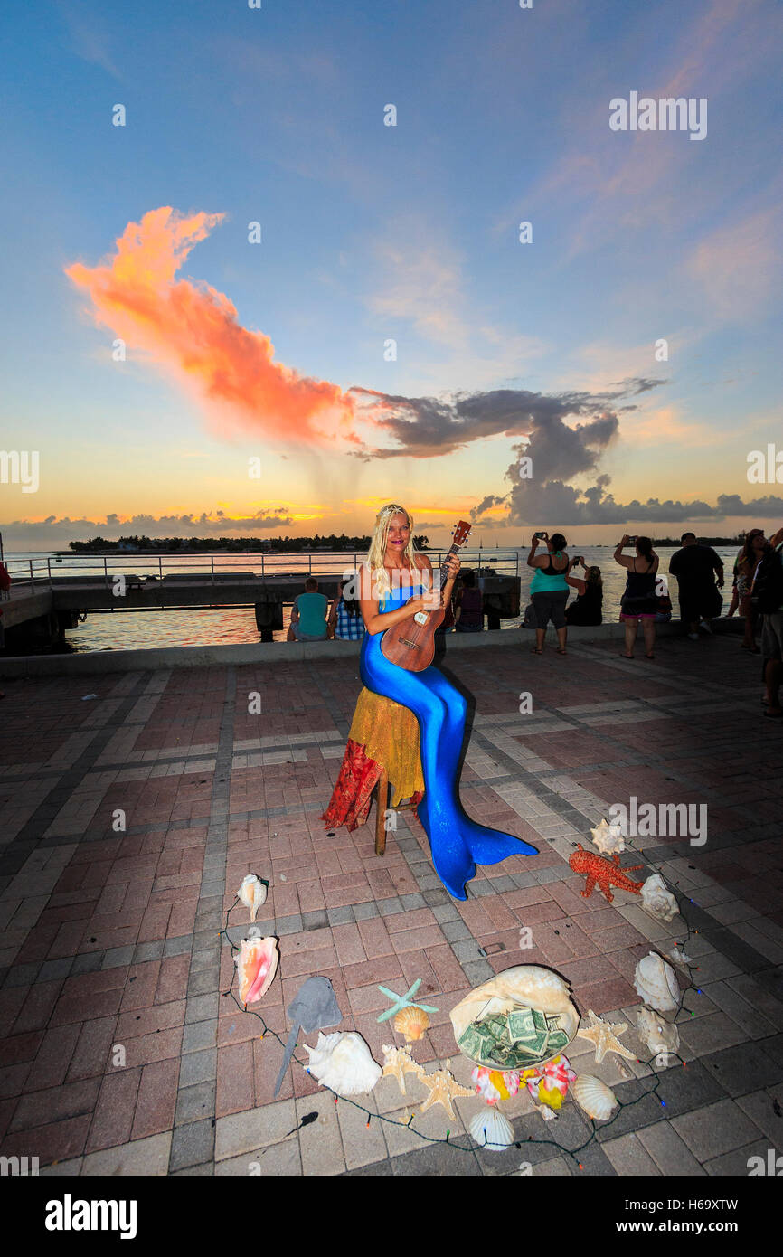 Crazy, joyous sunset scene nightly at Mallory Square in Key West. Here, a 'mermaid' plays her guitar. - Stock Image