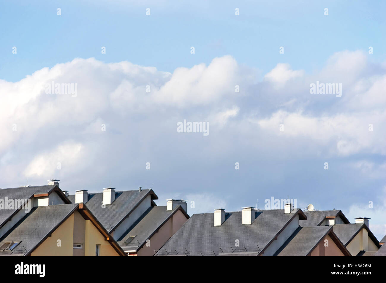 Row house roofs, apartments condo rooftops panorama and bright sunny summer clouds cloudscape - Stock Image