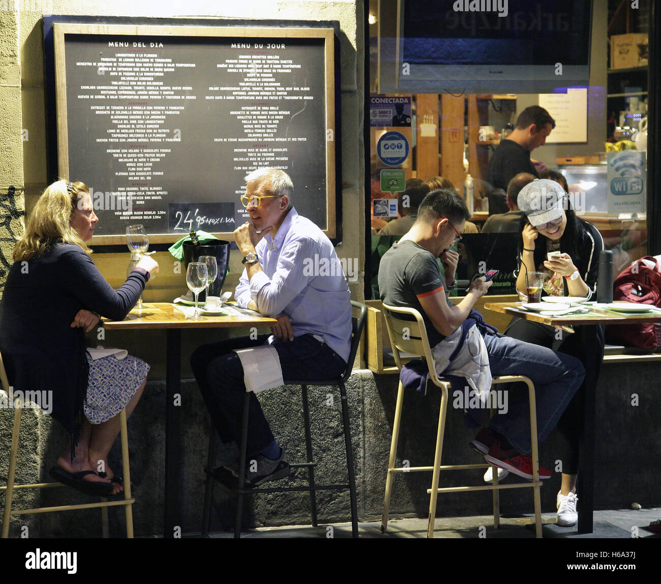 Outside diner at night with smartphones - Stock Image