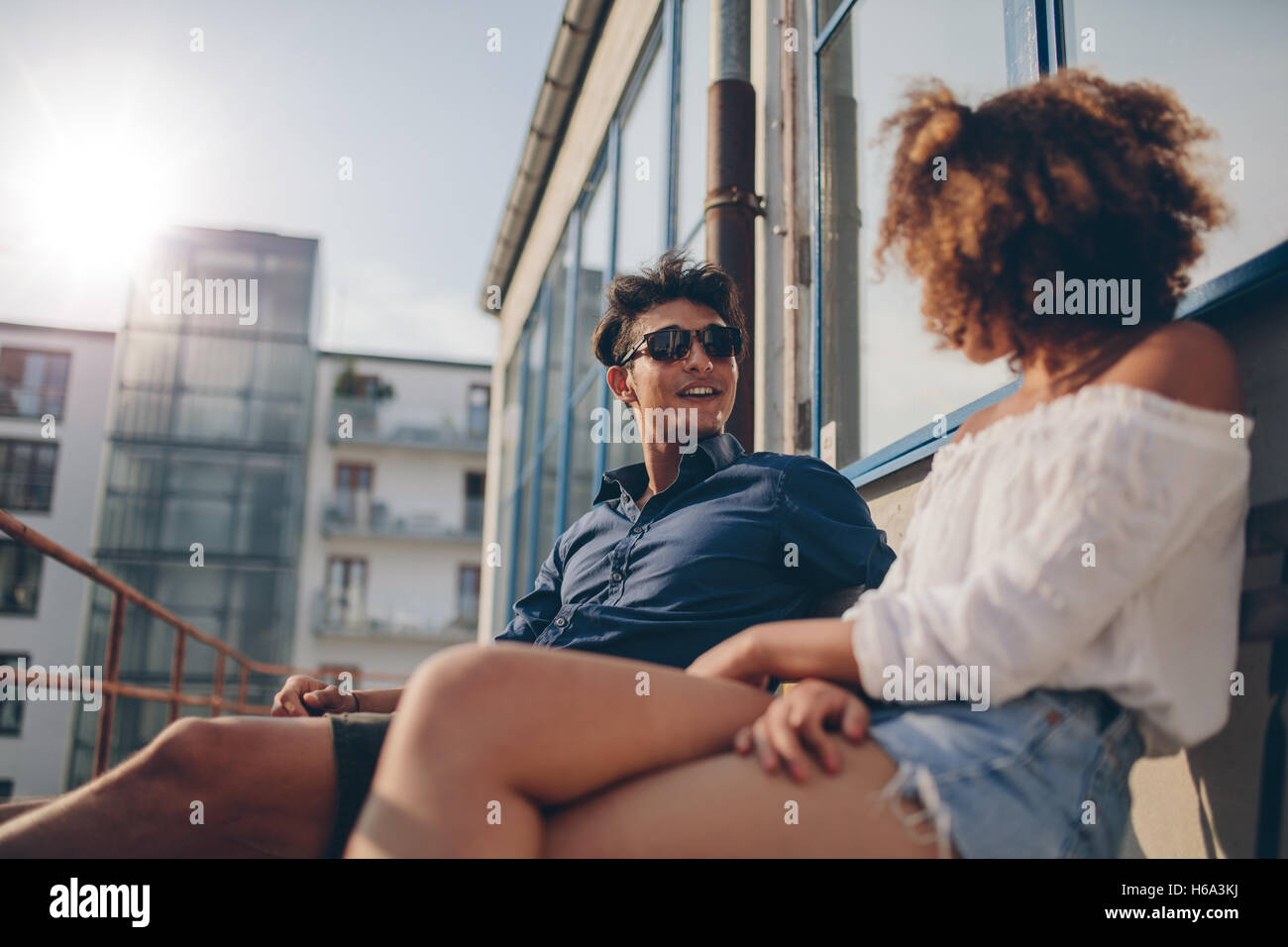 Young man and woman sitting in the balcony and talking. Young couple spending quality time together. - Stock Image