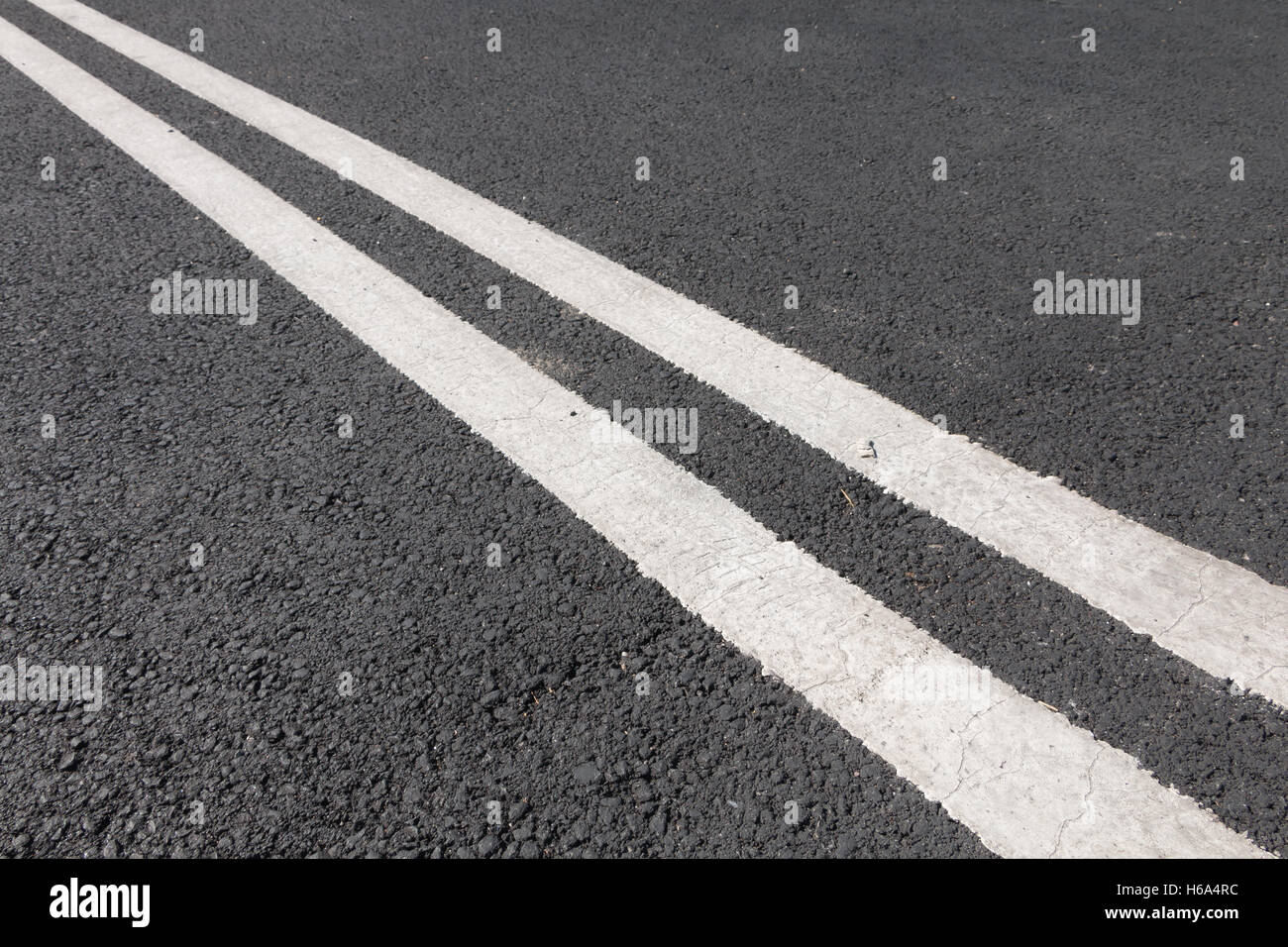 double white line diagonally across the black road - Stock Image