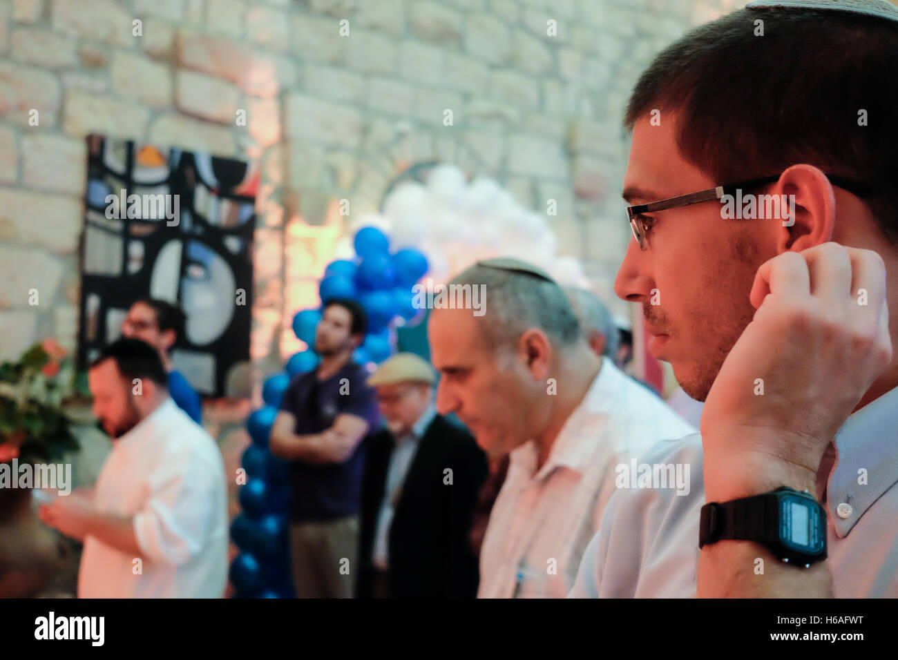 Jerusalem, Israel. 26th October, 2016. Jewish men congregate in a corner of a hall for evening prayers. Republicans - Stock Image