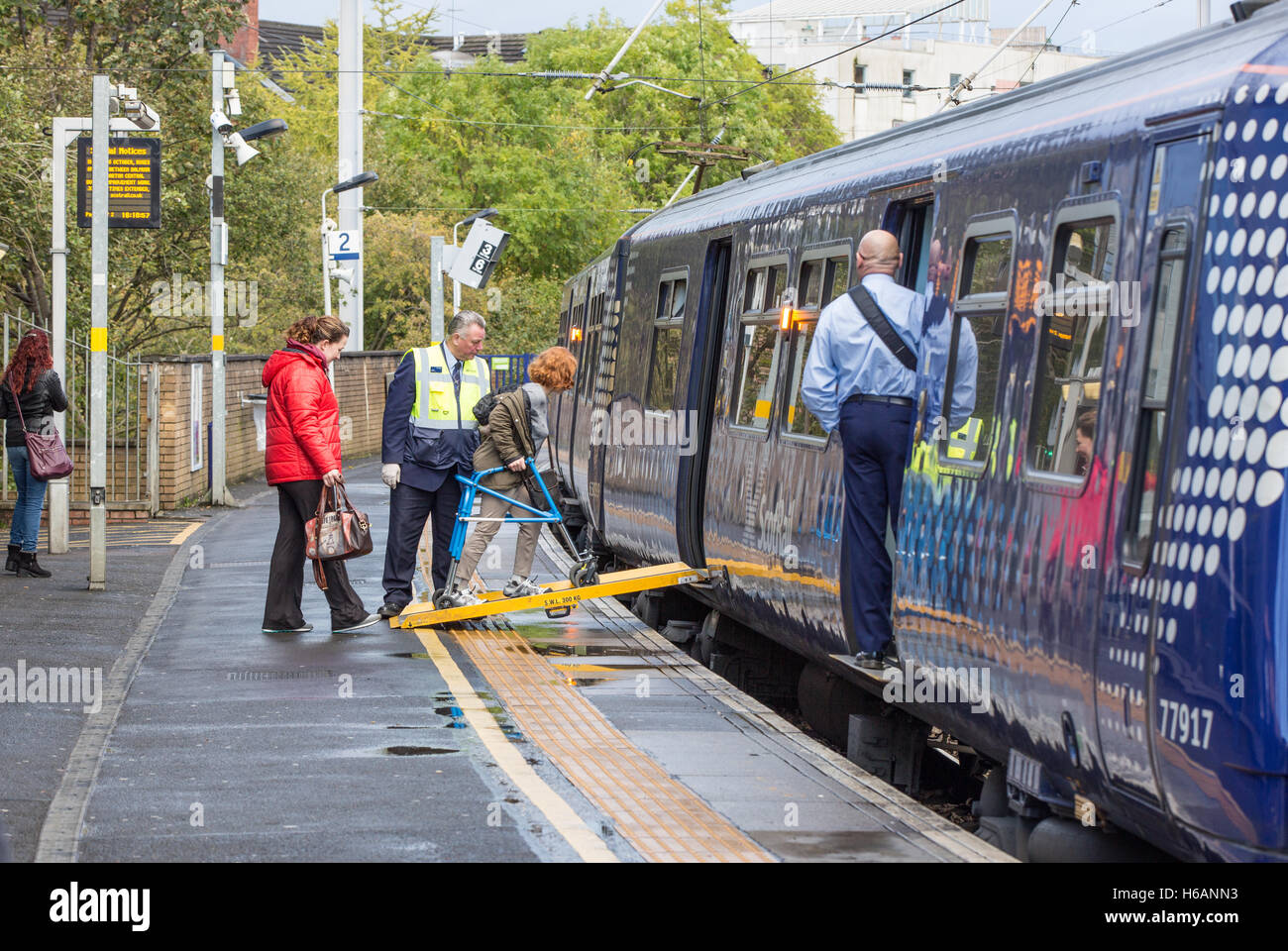 At Partick Train Station a passenger uses the disabled ramp to board a train. - Stock Image
