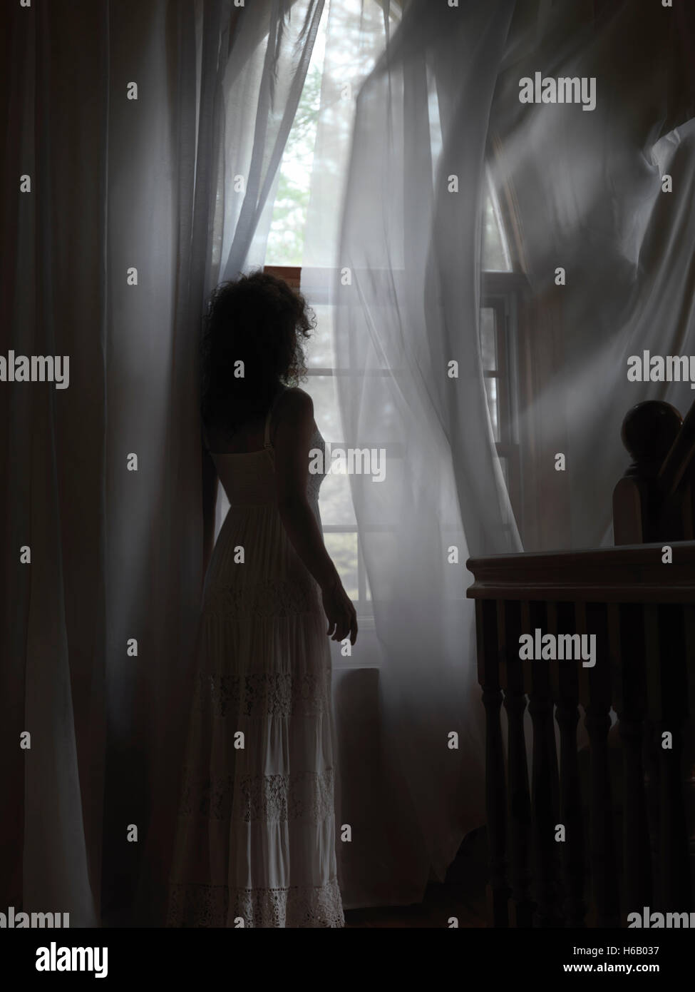 Artistic dramatic photo of a young woman in a dress standing by a window with flying in the wind curtains in a dark - Stock Image