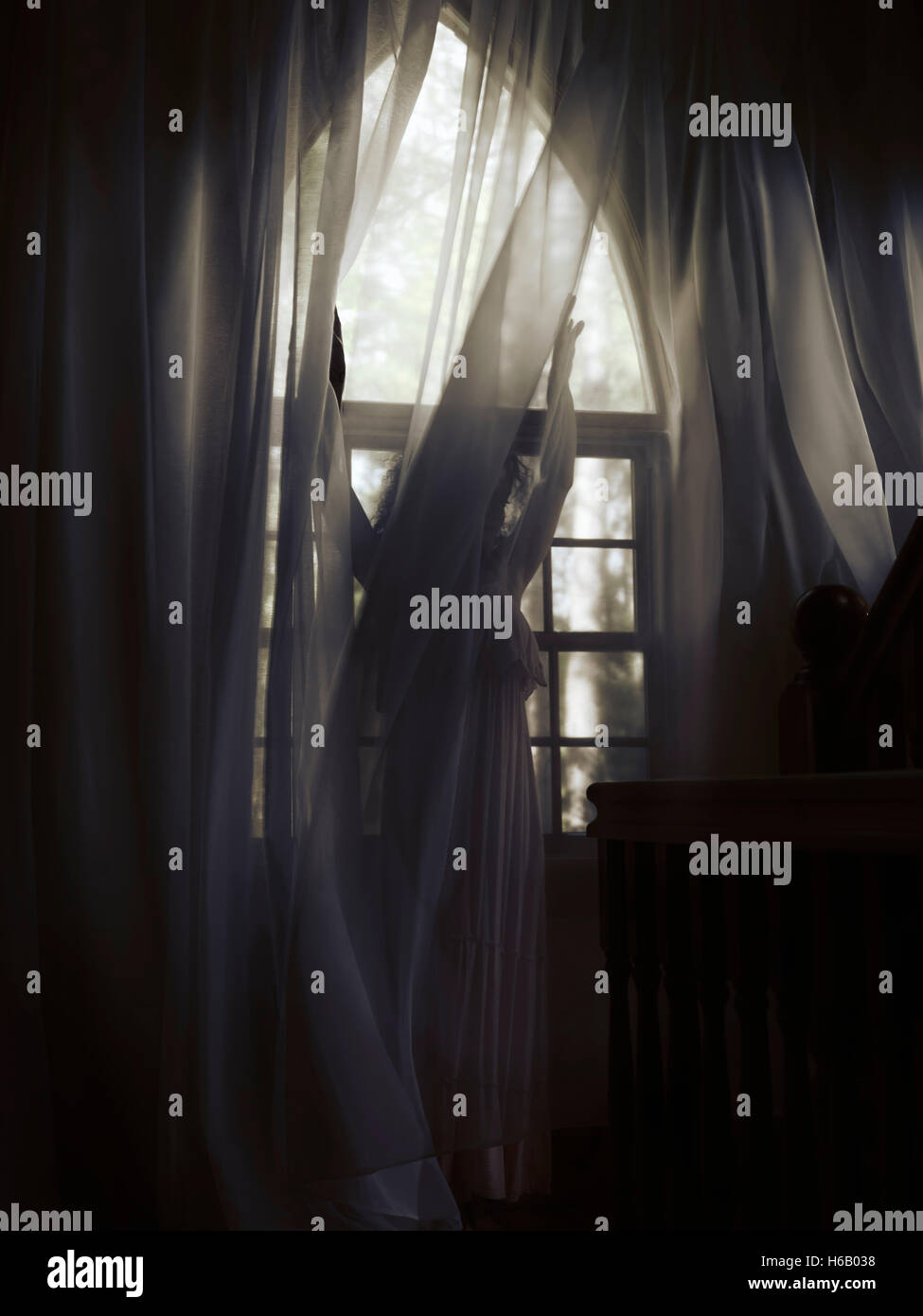 Artistic dramatic photo of a young woman in a dress standing behind the curtain by a window in a dark room of a Stock Photo