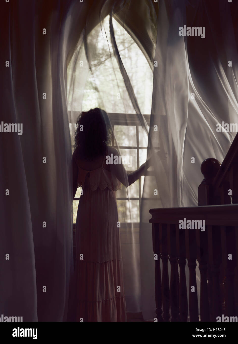 Woman in a long dress standing by a window with flying in the wind curtains in a dark house lit by dim sunlight - Stock Image