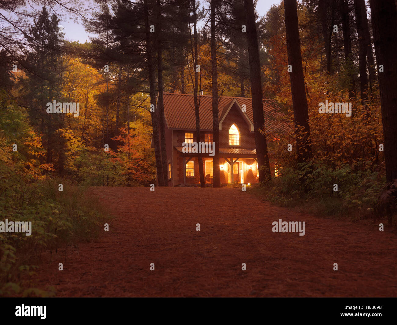 Brick country house or cottage with lights on in colorful autumn evening twilight nature scenery in Muskoka, Ontario, - Stock Image