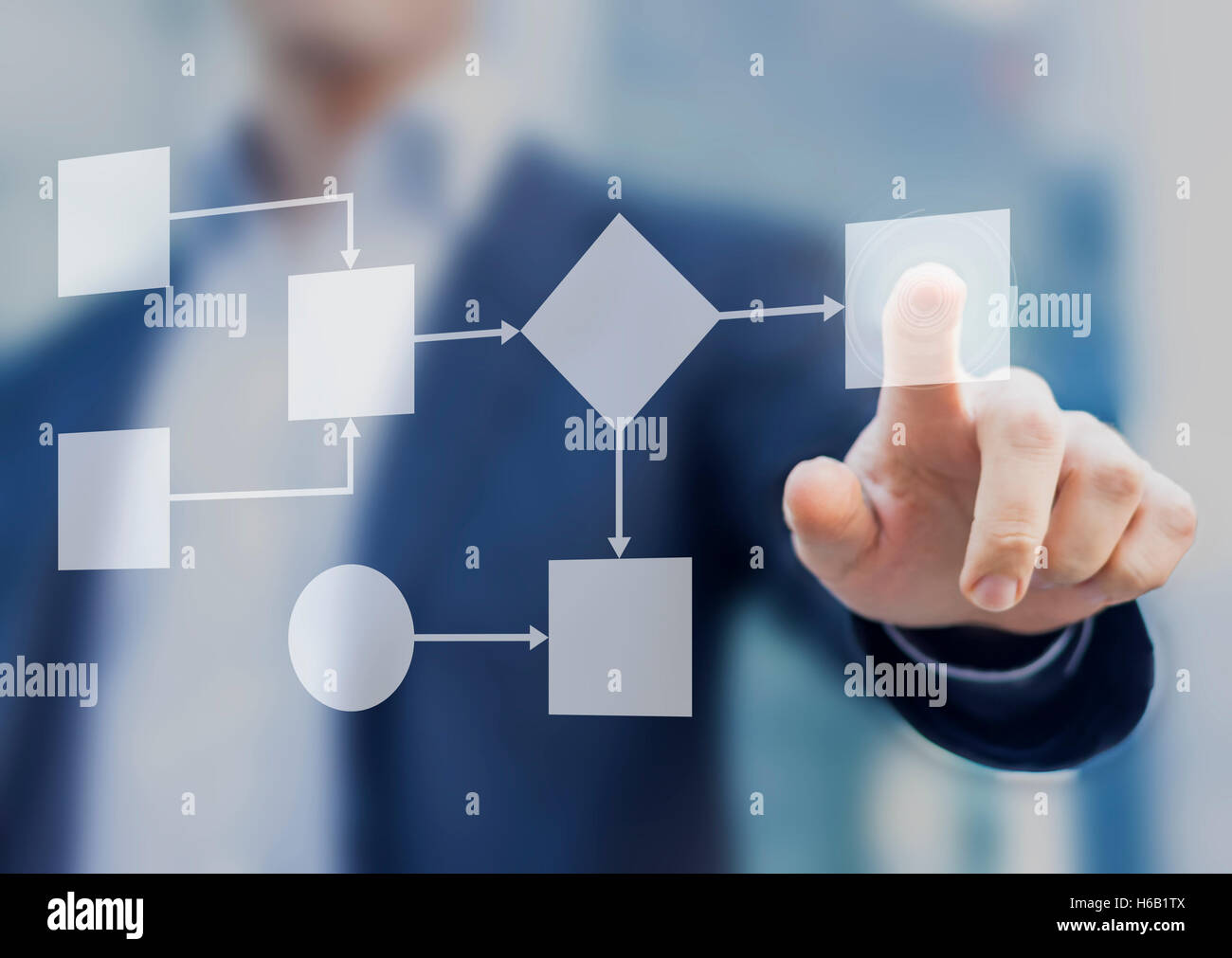 Business process and workflow automation with flowchart, businessman in background - Stock Image