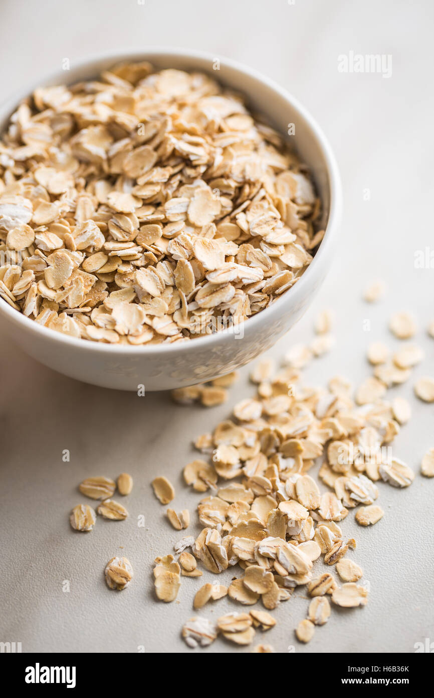Dry rolled oatmeal in bowl on kitchen table. - Stock Image