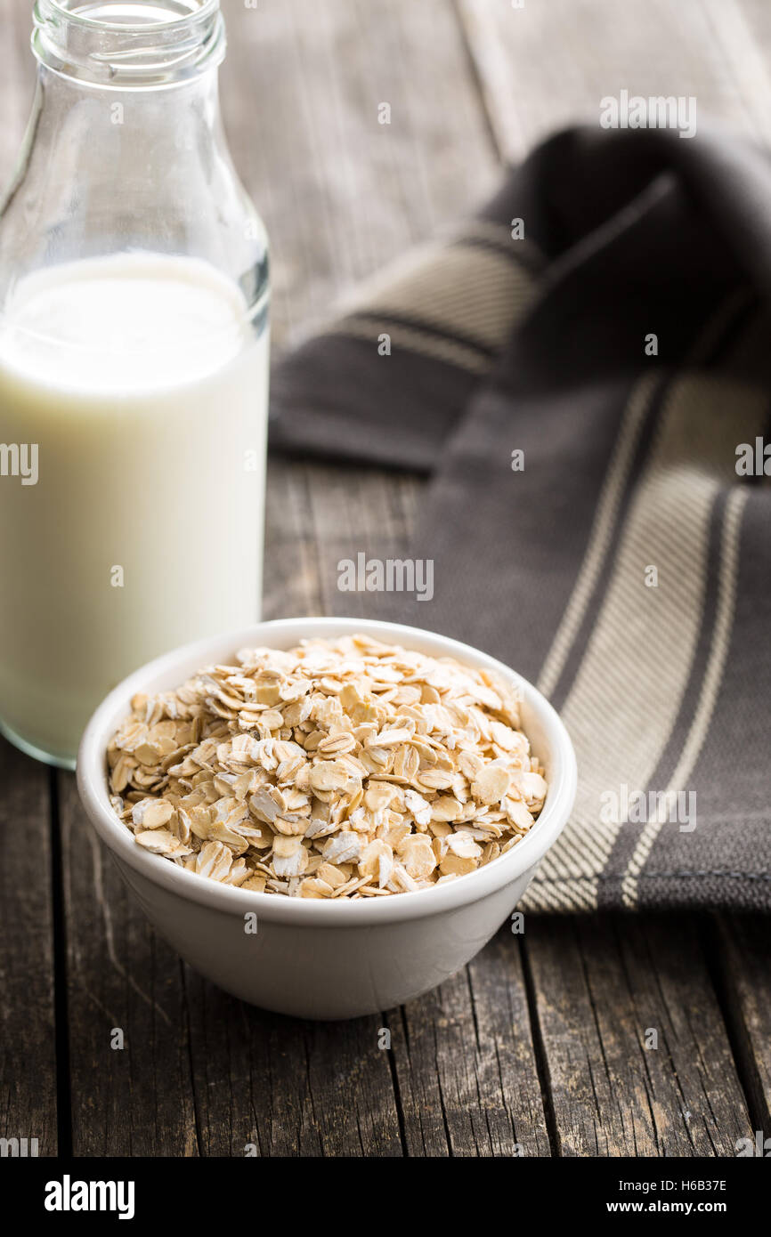Dry rolled oatmeal in bowl and milk in glass. Stock Photo