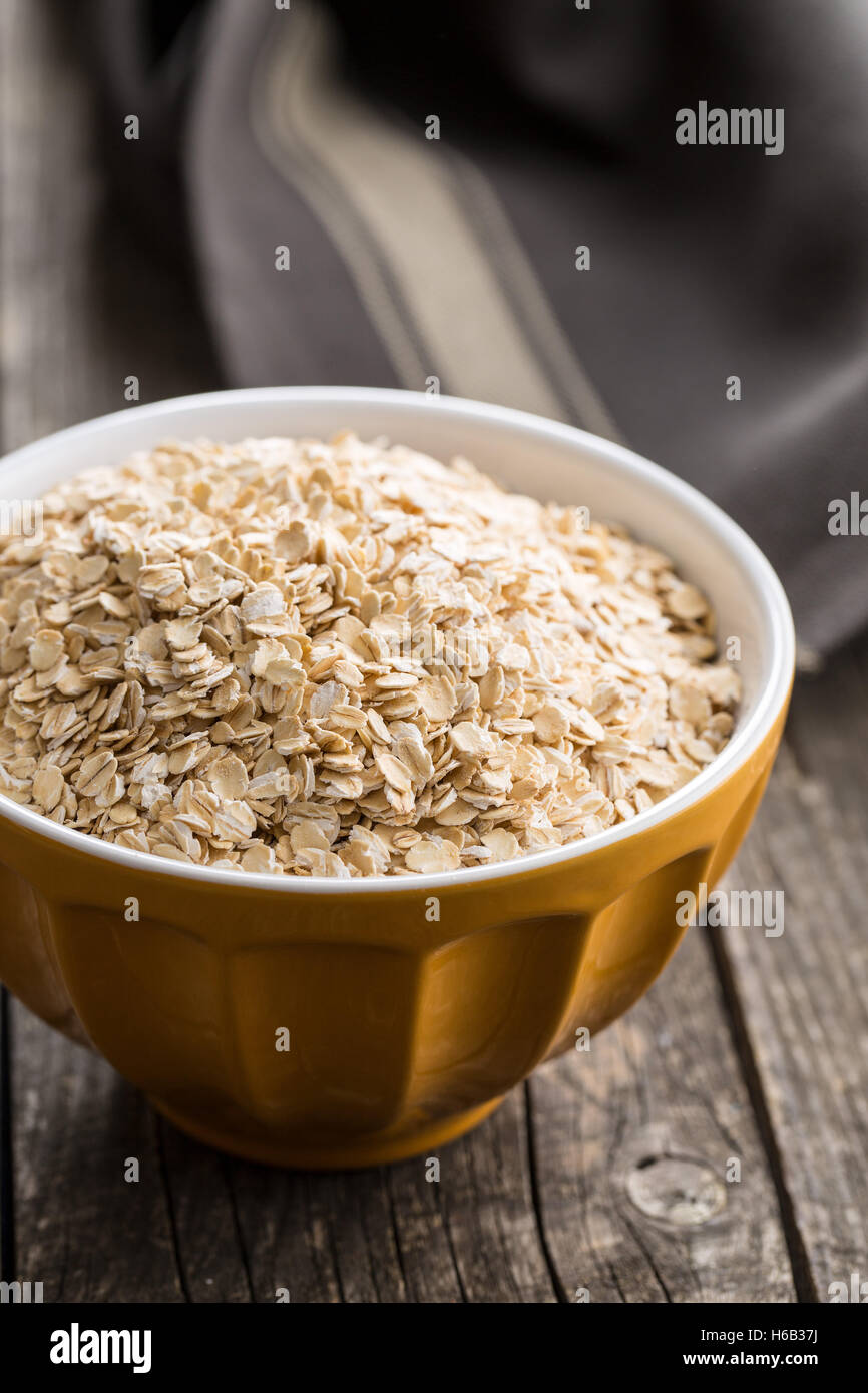 Dry rolled oatmeal in bowl on old wooden table. - Stock Image