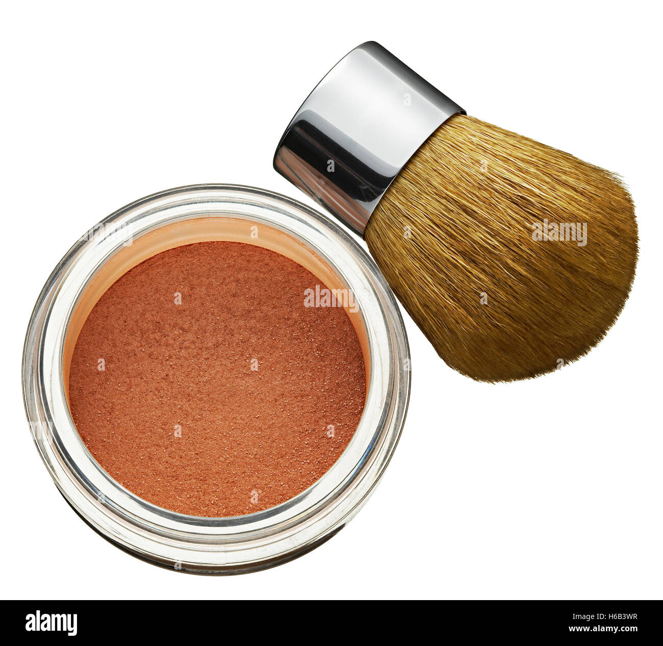 Glass jar of cosmetics foundation powder with a thick soft bristle brush for application in a high angle view conceptual - Stock Image