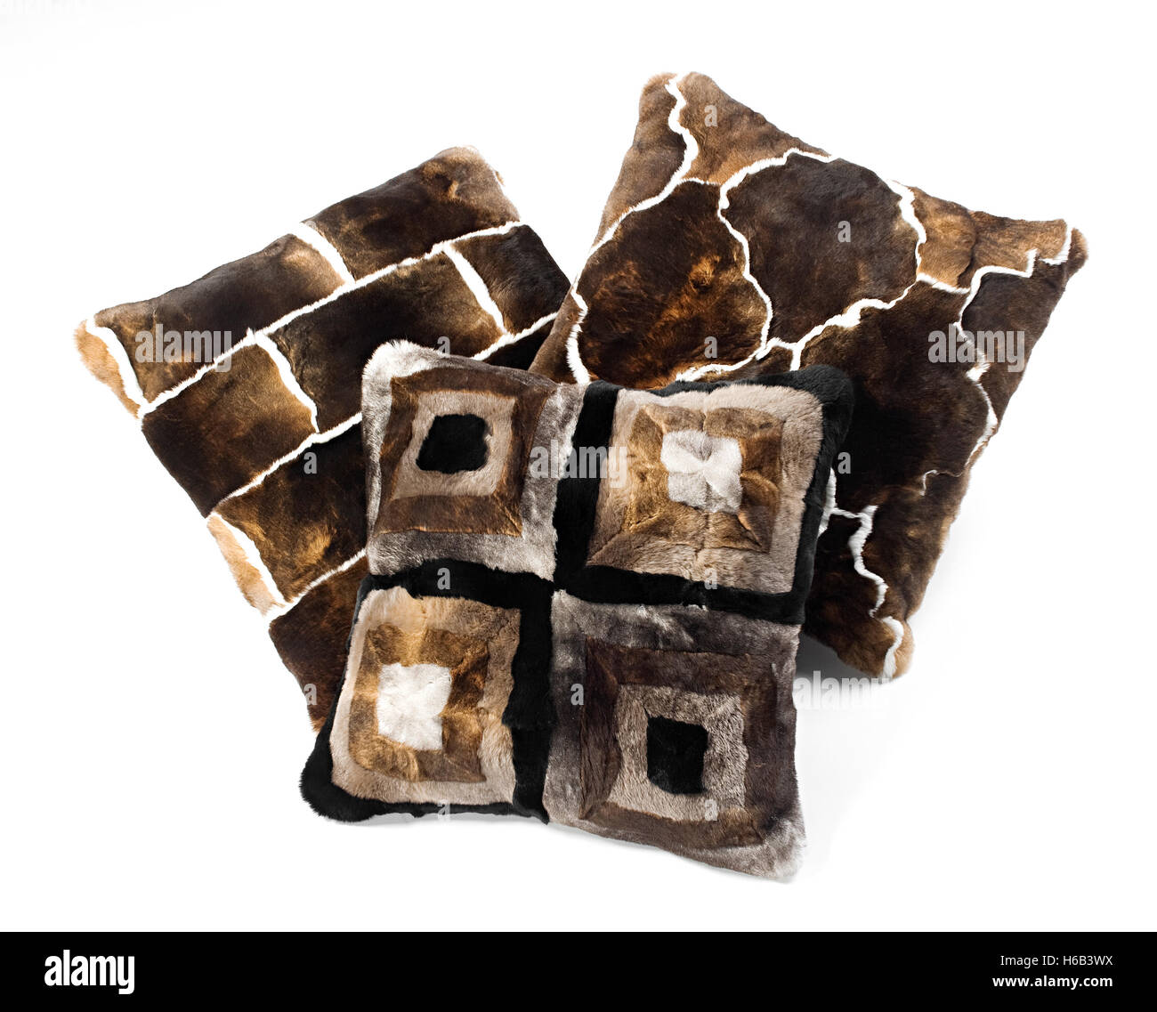 Three brown toned fur pillows with different bold geometric designs isolated on white in an interior decor concept - Stock Image