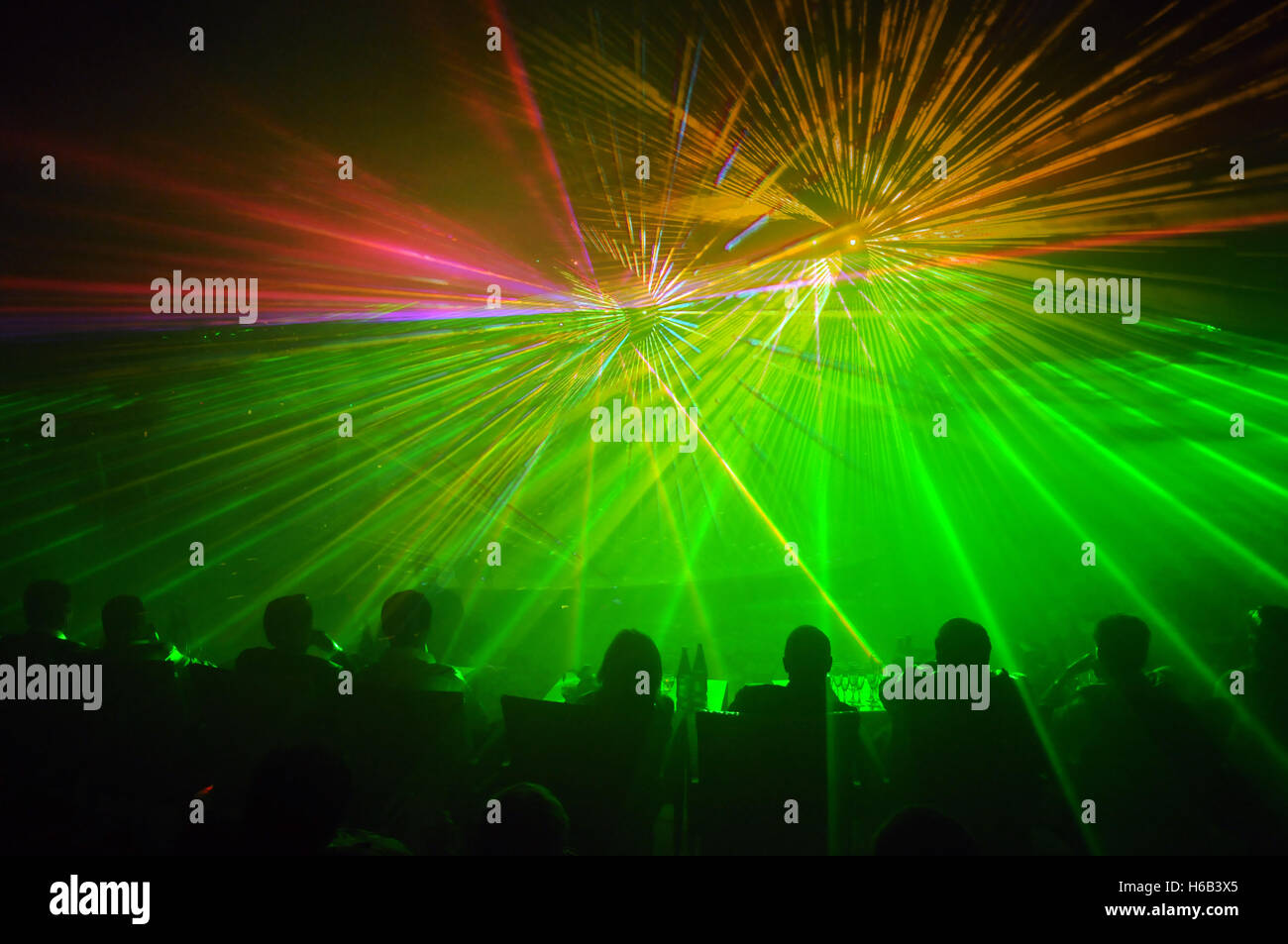 Row of people seated as audience members facing a green and yellow laser light show - Stock Image