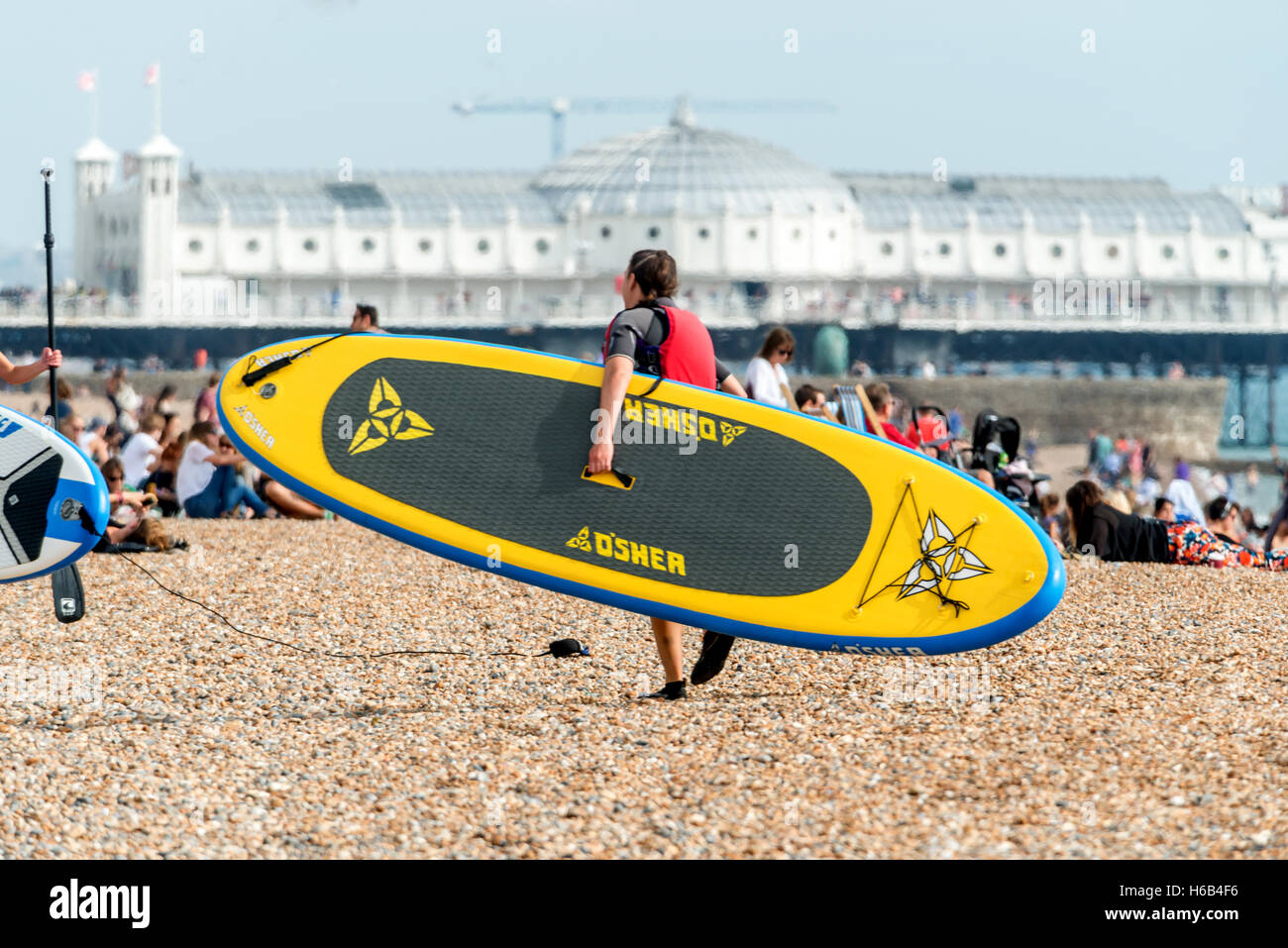 Surfers and sunbathers on Brighton beach - Stock Image
