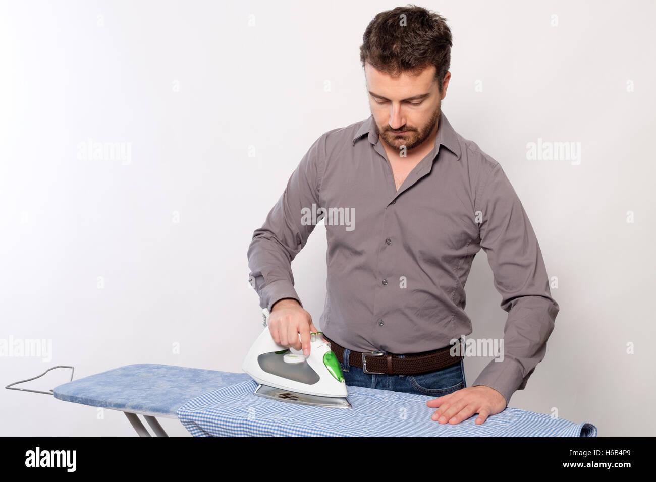 Portrait of single man ironing a shirt - Stock Image
