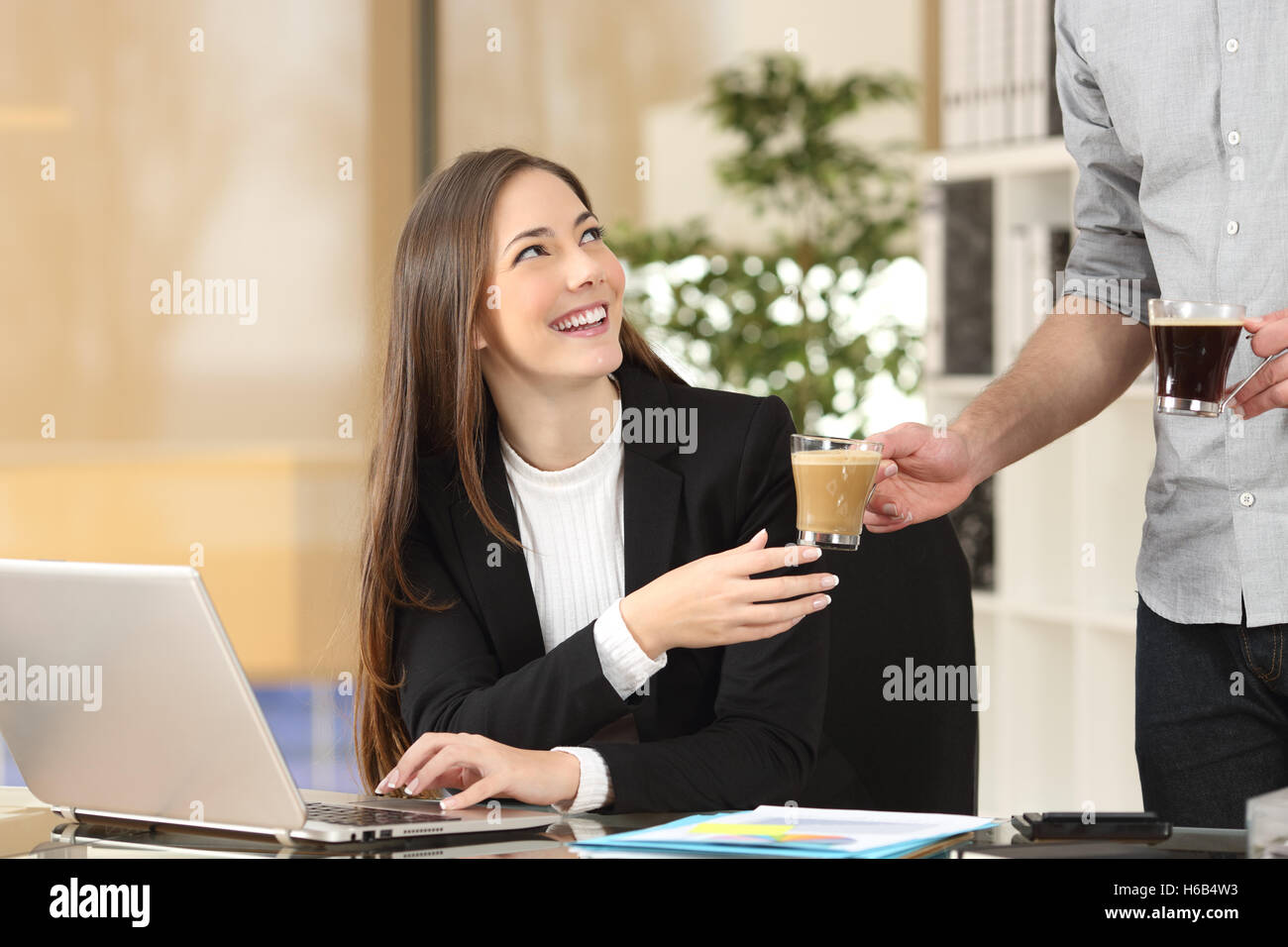 Businessman giving coffee to his colleague who is working with a laptop at office - Stock Image