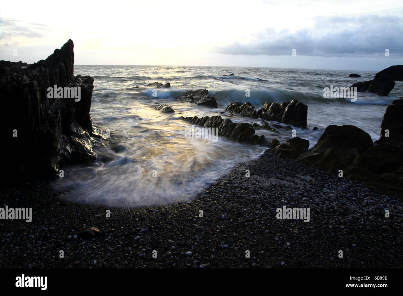 Gentle waves lap against the rocky shore at Ilfracombe as dusk approaches - Stock Image