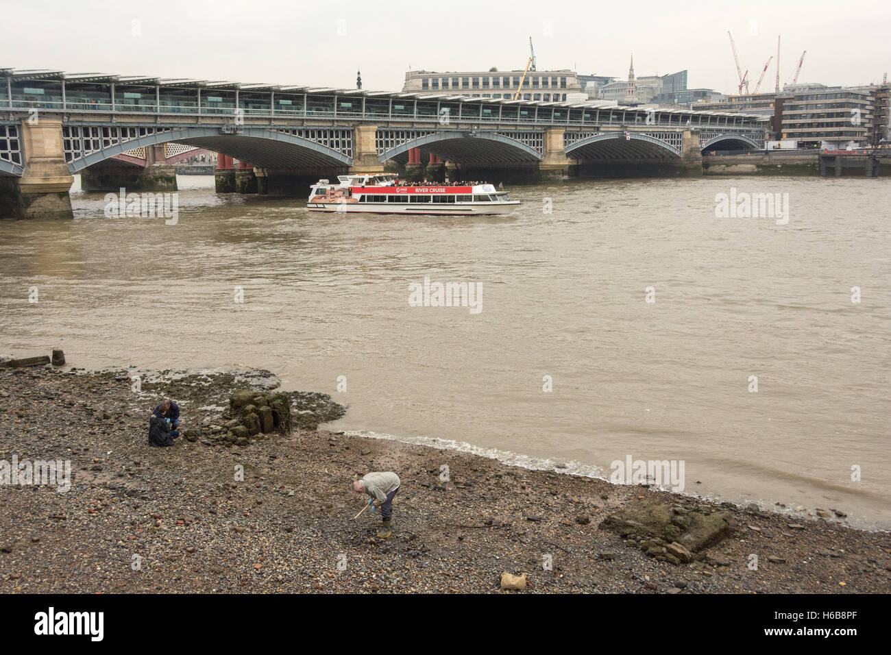 Mudlarking near Blackfriars Bridge on the River Thames in central London, UK. Stock Photo