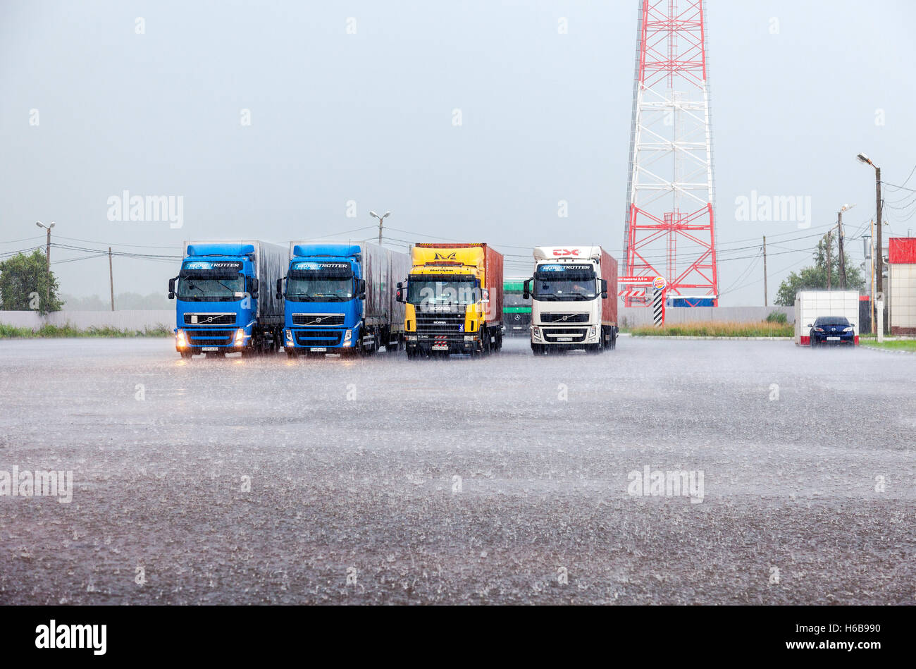 Truck trailers parked up at the parking lot in heavy rain - Stock Image